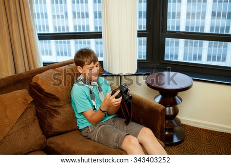 boy sitting on the couch with a camera in hand - stock photo