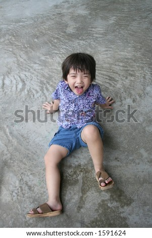 boy sitting on the floor happily making funny face - stock photo