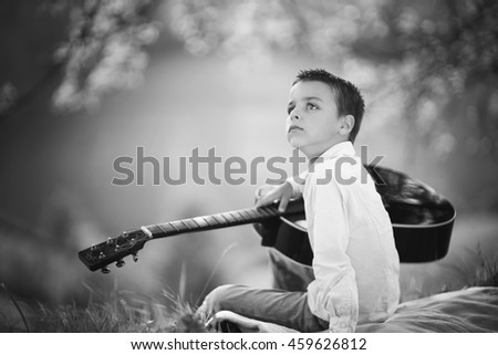 boy sitting with a guitar on a meadow before sunset summer days, black and white photography