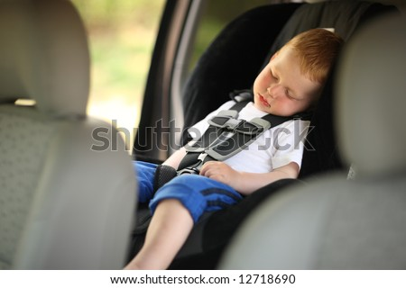 Boy sleeping in child car seat. Shallow DOF. - stock photo