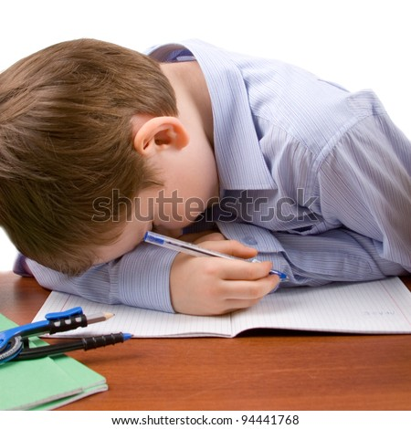 Boy sleeps at the table with books, isolated on a white background