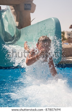 Boy sliding down a waterslide - stock photo