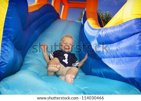 Boy sliding down an inflatable Side - stock photo