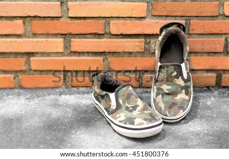 Boy small shoes army pattern on brick wall fashion concept