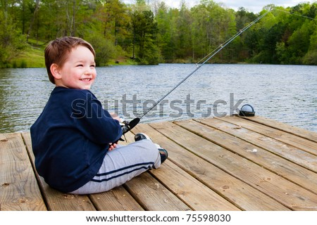 Boy smiles while fishing from dock on lake. - stock photo