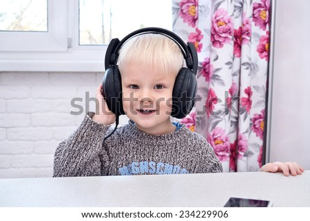 Boy smiling and listening to music in black earphones