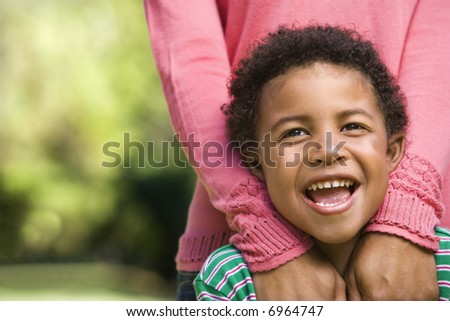 Boy smiling with mother standing behind him with hands on shoulders.
