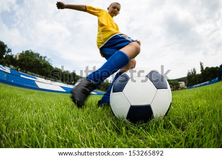 Boy soccer player hits the ball on the football field. Fish-eye lens. - stock photo
