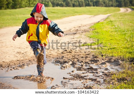 Boy splashing in puddle, having fun - stock photo