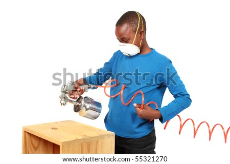 Boy spray painting with a spray gun and compressor - stock photo