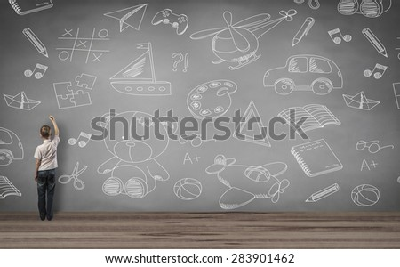 boy standing and writing in the wall - stock photo