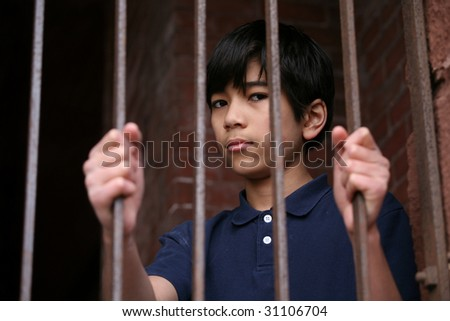 Boy standing behind bars, sad  or wary expression