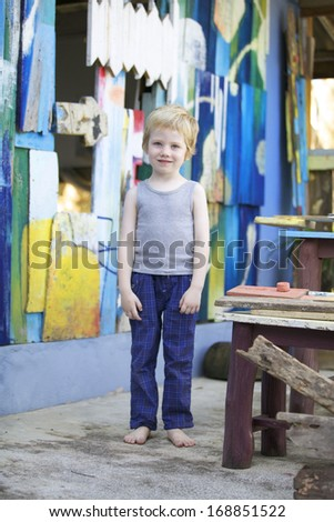 Boy standing in front of wooden boards painted in bright colors.