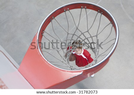 Boy standing looking up through basketball hoop - stock photo