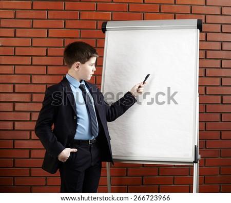 Boy standing near white office board. - stock photo