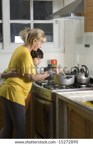 Boy standing next to woman with arm around waist. Boy watching woman stir pot on stove. Vertically framed photo. - stock photo