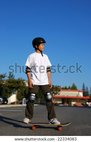 boy standing on a skateboard in an afternoon sun with blue sky in the background - stock photo