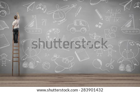 boy standing on staircase and writing in the wall - stock photo