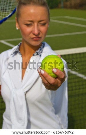 Boy standing with tennis racket and ball on the court