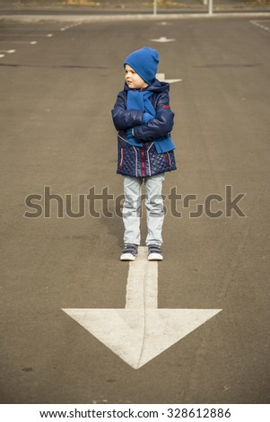 boy stands on the arrow on the road, abstraction