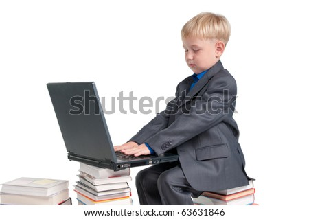Boy studying his lessons while sitting on a pile of books - stock photo