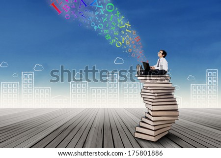 Boy studying with laptop while sitting on a pile of books - stock photo