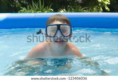 Boy swimming in garden pool with mask and snorkel - stock photo