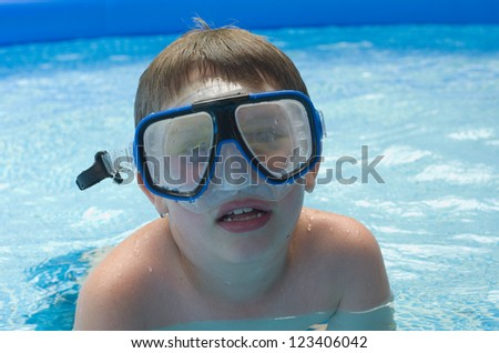 Boy swimming in pool with diving mask