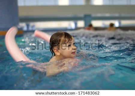 Boy swimming with swim noodle in the pool - stock photo