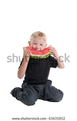 Boy taking a bite from a slice of juicy watermelon - stock photo