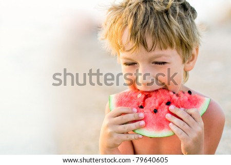 boy taking a bite of watermelon - stock photo