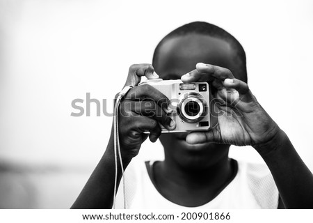 boy taking a photograph with a point and shoot camera - stock photo