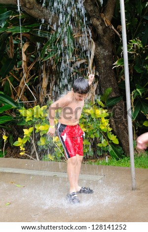 Boy taking shower outside - stock photo