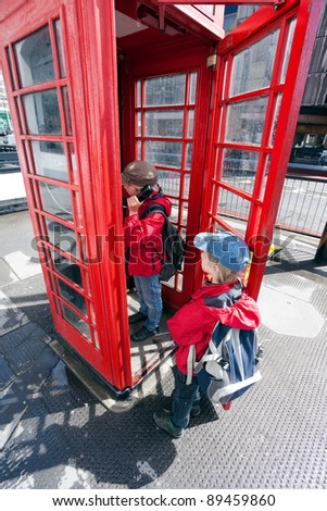 Boy talking in traditional red London pay phone box - stock photo