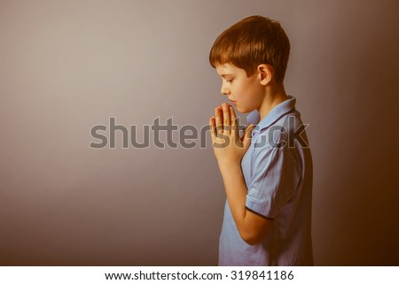 boy teenager European appearance in a blue shirt brown hair hung his head closed his eyes on a gray background, prayer retro - stock photo