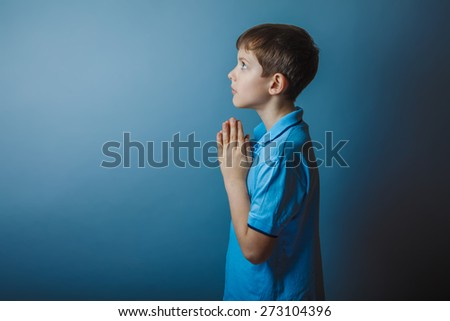 boy teenager European appearance in a blue shirt brown praying laid his head on a gray background, faith - stock photo