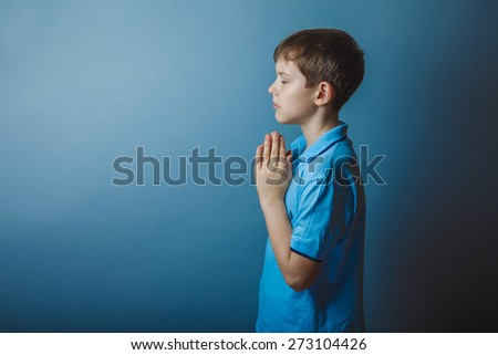 boy teenager European appearance in a blue shirt brown praying laid his head on a gray background, faith, hope, - stock photo