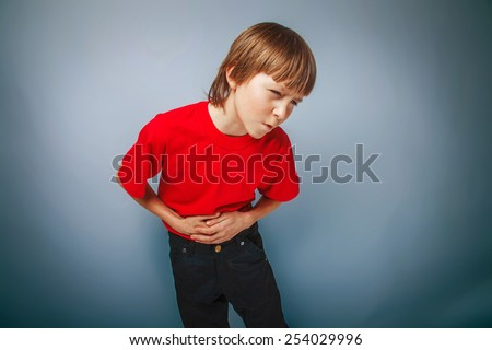 boy teenager European appearance in a red shirt holding his hand over his stomach on a gray background, pain cross process - stock photo