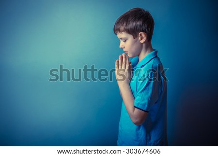 Boy teenager European appearance ten years stands sideways praying on a gray background retro photo effect - stock photo