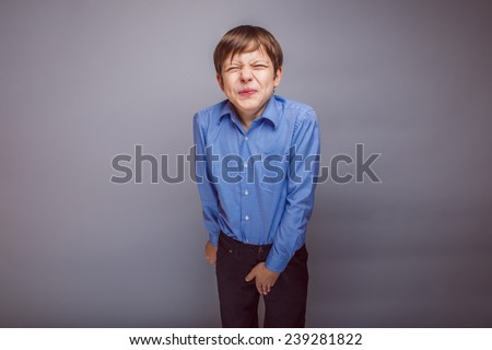 boy teenager European appearance winced his hand on the groin on a gray background - stock photo