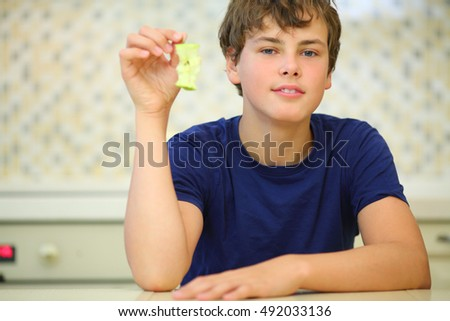 Boy teenager in dark blue shirt holds stub of green apple, close up view