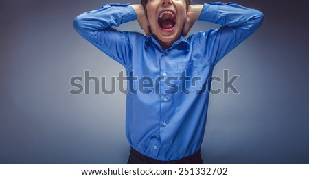 boy teenager of European appearance brown hair closed his ears shouting on gray background unknown - stock photo