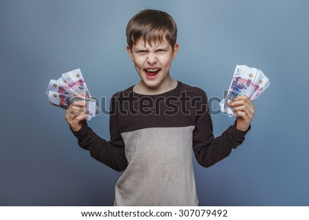 Boy teenager ten years  European appearance holding a wad  of money winner on a gray  background