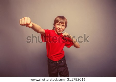 Boy, teenager, twelve his years  red  in shirt, red showing  fists retro - stock photo