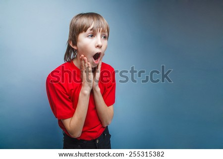 Boy, teenager, twelve years in the red shirt surprised open mouth
