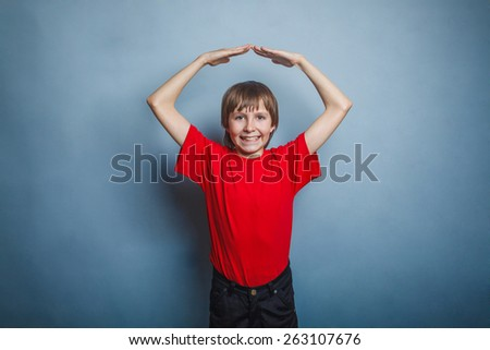 Boy, teenager, twelve years in the red t-shirt, made his hands above his head house - stock photo