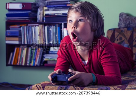 Boy teenager with remote control in hand playing a video game console.