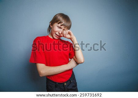 Boy, teenager, years  twelve red in T-shirt, hand wipes tears, sadness - stock photo