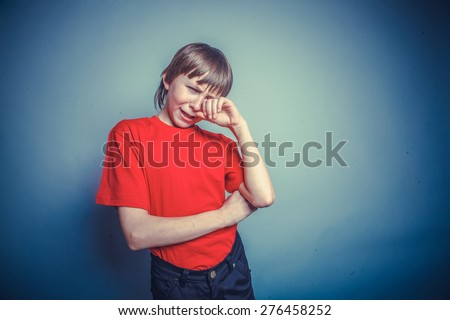 Boy, teenager, years  twelve red in T-shirt, hand wipes tears, sadness instagram effect style - stock photo