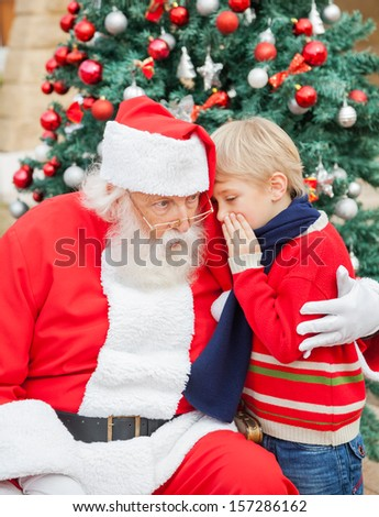 Boy telling wish in Santa Claus's ear in front of Christmas tree - stock photo